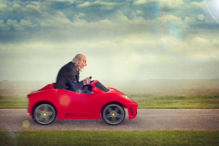 auto insurance refund Senior Man Driving A Toy Racing Car