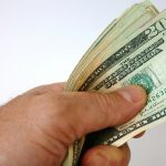 Private insurance - Hand holding US dollars
