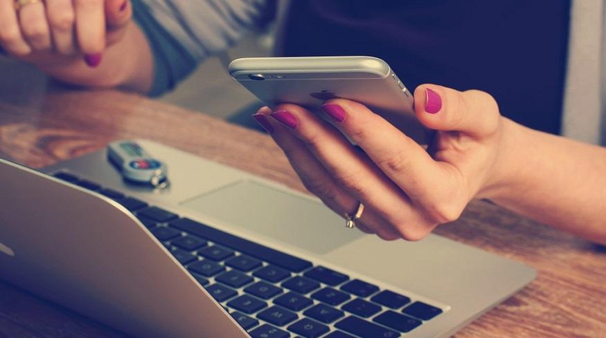 Digital insurance platform - Woman using smartphone and laptop