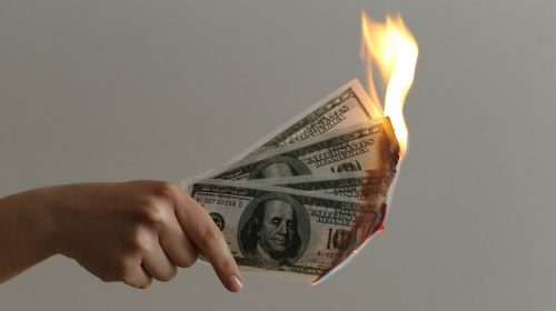 Pacific Gas and Electric - person holding money on fire