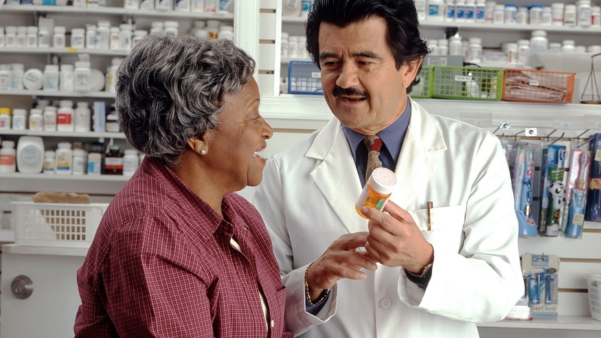 Health insurance individual mandate - woman receiving medication from pharmacist