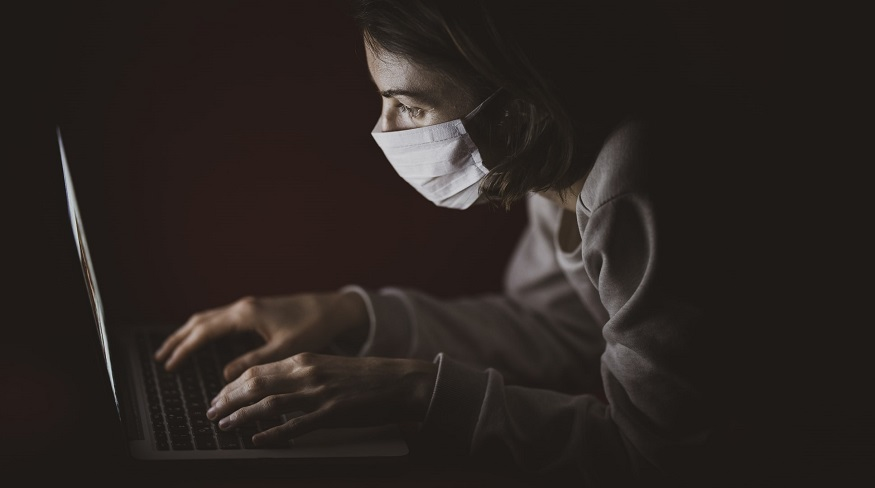 Life insurance policy - person wearing mask using computer