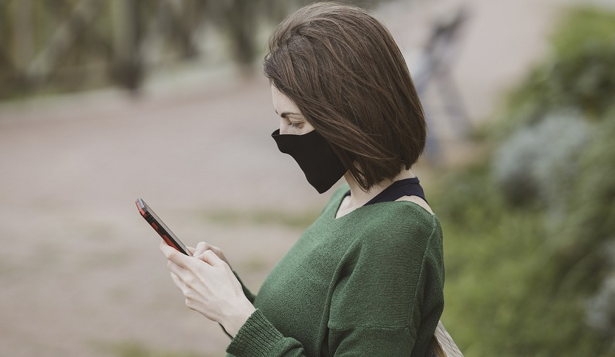 COBRA Insurance - Woman Looking at Phone sitting on bench wearing mask