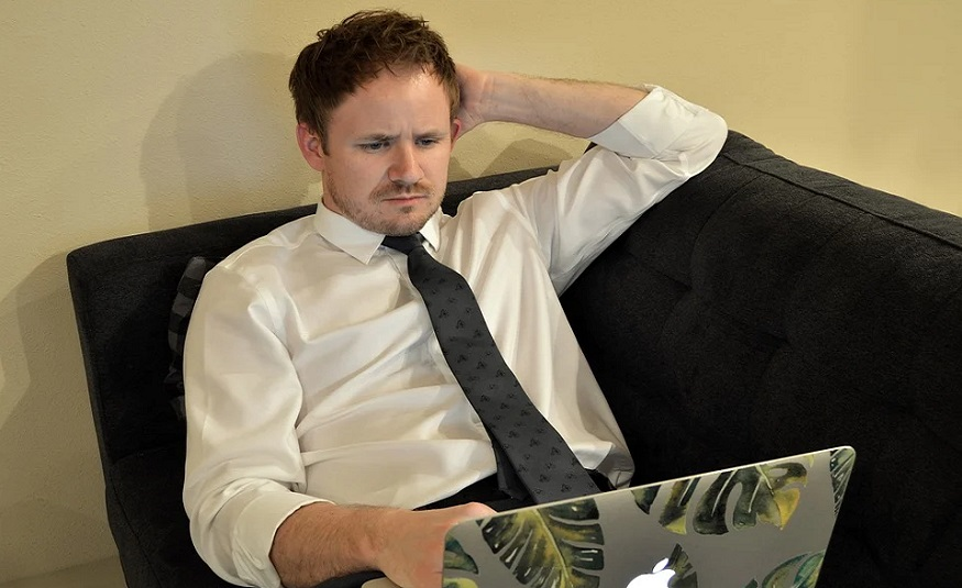 Life insurance policy trends - man looking thoughtful at laptop