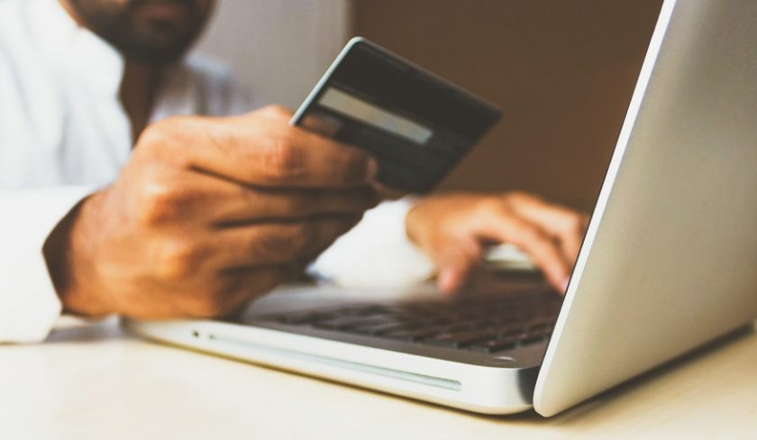 Washington insurance rate calculation - person holding credit card and using computer