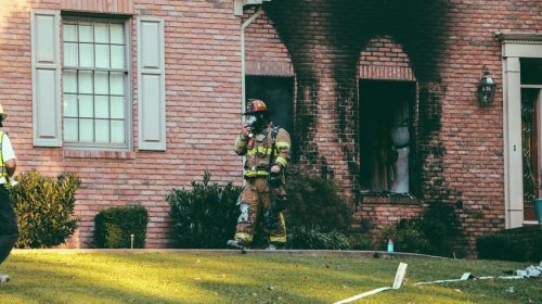 Wildfire preparedness - firefighter and scorched home